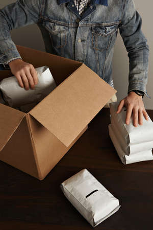 hermetic: Bearded brutal man in jeans work jacket puts blank sealed hermetic packages inside big carton paper box on wooden table. Special delivery, retail shipping post box top view