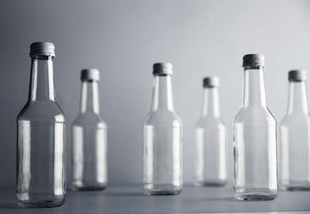 unlabeled: Set of empty cristal unlabeled bottles randomly presented on gray surface, isolated, close focus frontal bottles