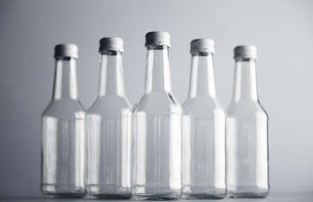 unlabeled: Clear unlabeled transparent bottles for cider or alcohol drinks presented in center, closed with metal white caps, isolated on gray background