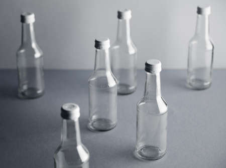 unlabeled: Set of empty cristal unlabeled bottles randomly presented on gray surface, closed with sealed white metal caps, isolated, top view LANG_EVOIMAGES