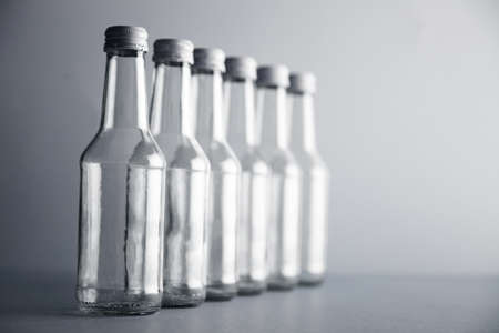 unlabeled: Set of unlabeled empty transparent bottles closely isolated in row line on side on simple gray background, first bottle in focus, others unfocused in bokeh LANG_EVOIMAGES