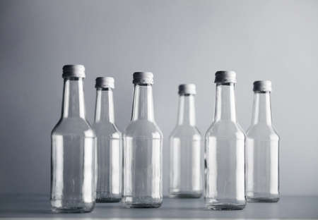 unlabeled: Set of empty cristal unlabeled bottles randomly presented on gray surface, isolated
