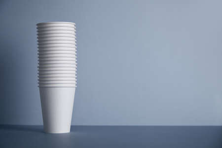 Many white paper cups folded one in other in big bunch, isolated on left on simple gray background Фото со стока