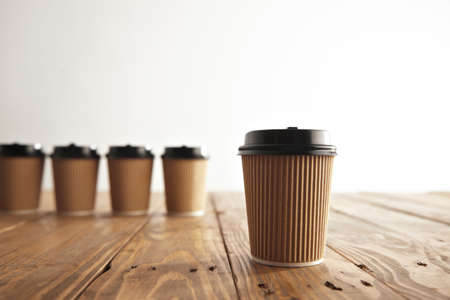 cup four: One focused cardboard paper coffee cup with black cap isolated on side in front of unfocused four take away cups on brushed vintage wooden table