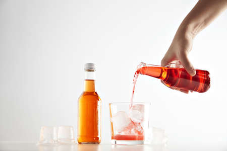 unlabeled: Hand pours berry cider drink into glass with ice cubes near sealed closed unlabeled bottle with orange aperol
