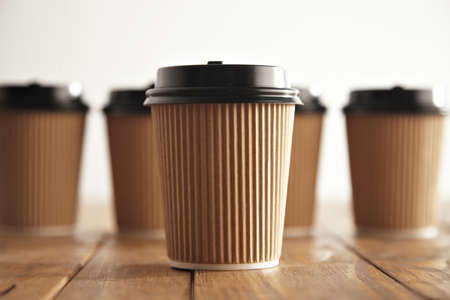 vintage: One focused craft paper coffee cup with black cap isolated in center in front of unfocused group of others on vintage brushed pallet table close view
