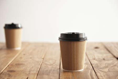 Metta a fuoco la tazza di carta del cartone con il cappuccio dentro isolato nel centro e l'altro unfocused sulla parte della tavola di legno rustica