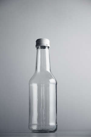 unlabeled: Empty unlabeled glass transparent bottle isolated on gray background in center