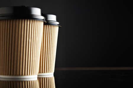 Brown porta via bicchieri di carta chiusi con tappi isolati a sinistra, sfondo nero e immagine speculare. Presentazione di mockup di vendita al dettaglio Archivio Fotografico