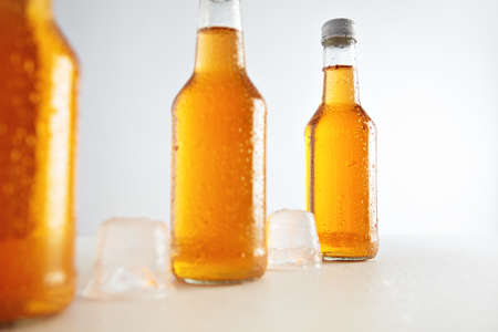 unlabeled: Closeup unlabeled rustic bottles sealed with tasty cold drink inside presented next big ice cubes, isolated on white, retail mockup presentation