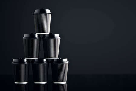 Luxury set of black take away cardboard paper cups closed with caps isolated on black in pyramid shape. Retail mockup presentation