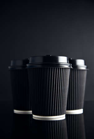 Luxury set of black take away cardboard paper cups closed with caps isolated on black and mirrored. Space for your text above