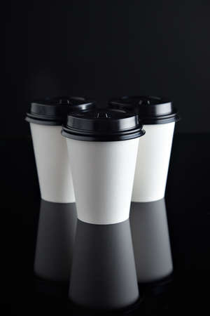 Set of three take away white coffee cardboard paper cups closed with black caps isolated in center and mirrored. Retail mockup presentation, top view Stock Photo