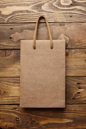 centimetre: Brown takeaway bag from thic recycled craft paper on rustic wooden table mockup