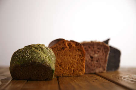artisan bakery: Pieces of different professional baked breads presented on wooden table as samples for sale: pistachio, dry tomato,lavender and coal. Close focus on green bread LANG_EVOIMAGES