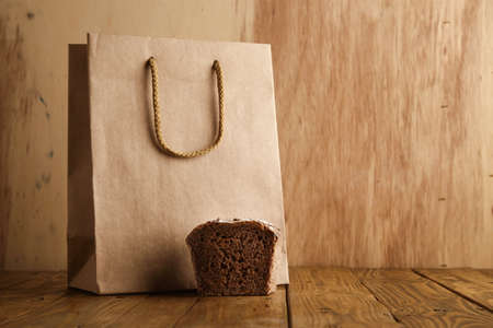 artisan bakery: Piece of brown rye bread presented near take away blank bag from craft paper in artisan bakery on wooden background LANG_EVOIMAGES