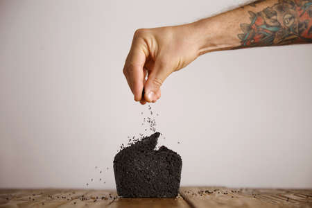 artisan bakery: Tattooed hand pours black seeds spices on top of black coal organic homemade bread isolated on craft paper on wooden table in artisan bakery