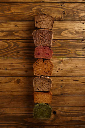 artisan bakery: Many mixed alternative baked breads presented as samples for sale in line on rustic wooden table in professional bakery: pistachio,beetroot,tomatoes,lavender,sea salt, coal,sweet potato