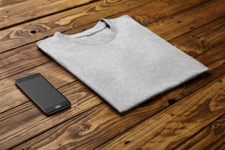 accurately: Blank grey t-shirt accurately folded near black smartphone gadget on rustic wooden table side view