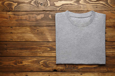 accurately: Blank grey t-shirt accurately folded on rustic wooden table top view mockup