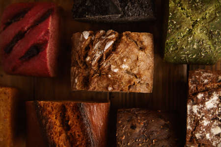 artisan bakery: Many mixed alternative baked breads presented as samples for sale on rustic wooden table in professional bakery: pistachio,beetroot,tomatoes,lavender,sea salt, coal,sweet potato Close up