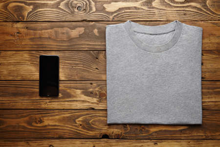 accurately: Blank grey t-shirt accurately folded near black smartphone gadget on rustic wooden table top view
