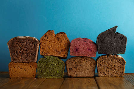 artisan bakery: Many mixed alternative baked breads presented as samples for sale on blue background in professional bakery: pistachio,beetroot,tomatoes,lavender,sea salt, coal,sweet potato