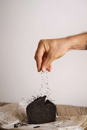 artisan bakery: Hand pours black seeds spices on top of black coal organic homemade bread isolated on craft paper on wooden table in artisan bakery