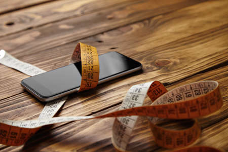 centimetre: Smartphone tied in tailoring meter presented on rustic wooden table close view