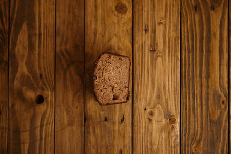 artisan bakery: Piece of black organic rye homemade bread on rustic wooden table top view