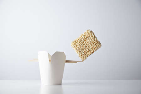 balances: Brick of dry noodles balances on the edge of chopsticks on blank takeaway box isolated on white commercial retail set mockup