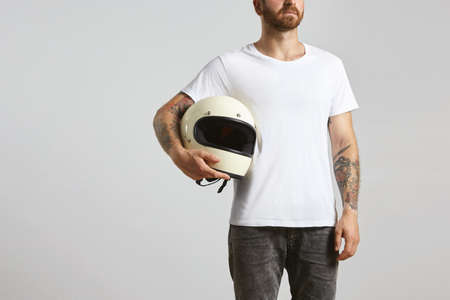 Attractive brutal tattooed bearded guy poses in black jeans and blank white t-shirt from premium thin summer cotton, holding motorbike helmet in hand, isolated on white mockup Фото со стока