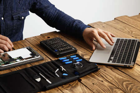 tool bag: Unrecognizable man uses laptop to find guides how to repair electronic device Tool bag and broken gadget near on vintage wooden table LANG_EVOIMAGES