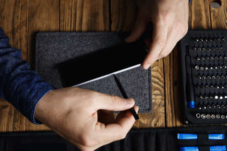 disassemble: Man uses special plastic stick to pull micro sim card tray out from mobile smart phone body Professional disassemble tools near