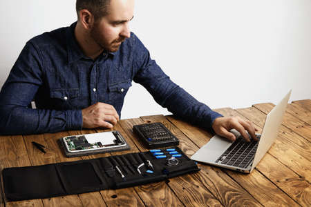 tool bag: Professional uses laptop to find internet guides how to repair electronic device Tool bag with instruments and broken gadget near on vintage wooden table LANG_EVOIMAGES