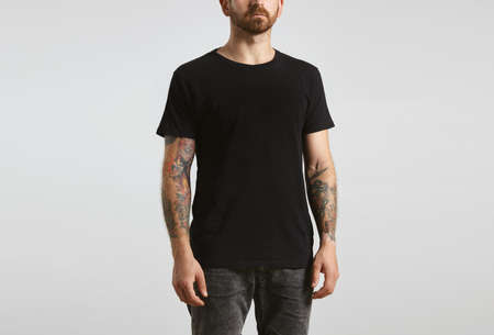 Brutal attractive bearded biker man with tattooed hands poses in black blank t-shirt from premium thin cotton, isolated on white mockup