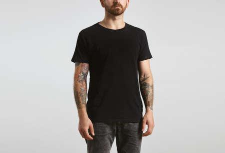 hombre con barba motorista atractivo brutal con las manos tatuadas plantea en negro en blanco t-shirt de algodón fino prima, aislado en blanco maqueta