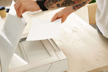 scan paper: Tattooed brutal hands put sheet of paper to scan a document on home multifunctional printer scanner device