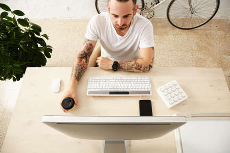 Top view tattooed freelancer holds coffee from take away paper cup while looking on his computer display with midi music controller at home desktop with smart phone on it.