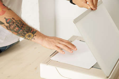 mfp: Hands open a scanner tray and put paper sheet to scan a document inside multifunctional electronic device, isolated on white wooden table,
