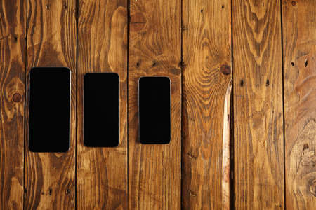 Top view on three generation of modern smartphones isolated on rustic wooden background