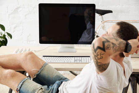 tattoed: Close focus on relaxing tattoed freelancer dreamily looking somewhere while taking break from work, with his legs on table inside big white loft