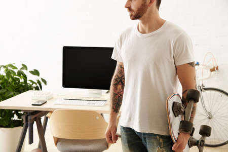 big shirt: Brutal tattoooed man in blank t-shirt holds surf skateboard in big loft in front of his working desktop with computer Vintage bicycle parked on background.
