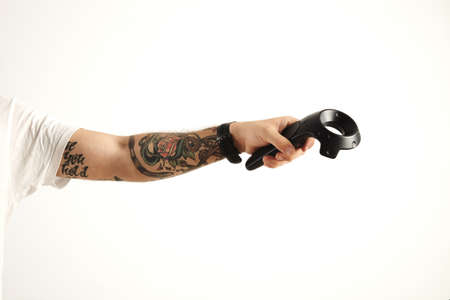 Tattoed hand holds vr remote controller, isolated on white Wireless joystick for next generation video games and consoles LANG_EVOIMAGES