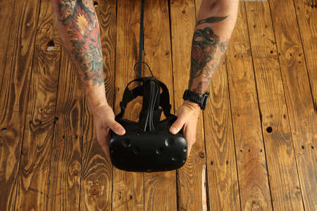 tattoed: Tattoed hands hold virtual reality goggles, presentation of new technology, isolated on rustic wooden background in center LANG_EVOIMAGES