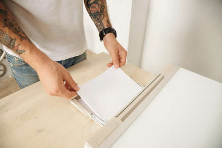 mfp: Tattooed hands charges home mft device with new pack of sheets of paper