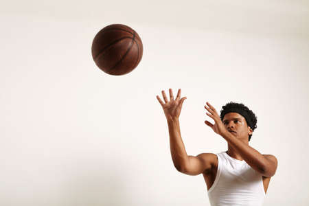 Focused attractive young African American player with an afro wearing white basketball shirt throwing a vintage leather basketball isolated on white