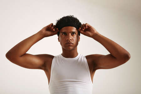 Muscular attractive African American athlete in white basketball shirt adjusting his black headband and looking slightly above the camera, isolated