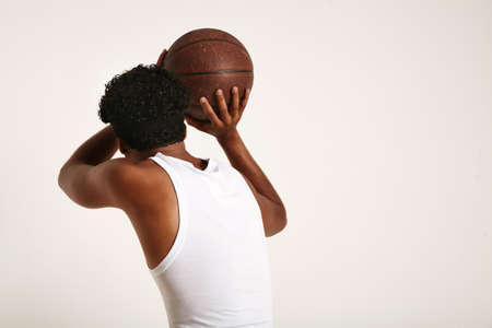 Back shot of a muscular dark skinned athlete with an afro and headband wearing white sleeveless shirt throwing an old brown leather basketball against white background.