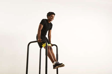 Low angle shot of a smiling strong African American athlete with an afro wearing black synthetic shirt and black and yellow shorts doing L-sits on short bars at home isolated on white. LANG_EVOIMAGES